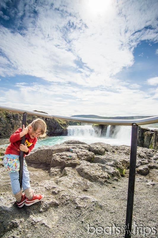 Niño jugando en cascada Godafoss Goðafoss